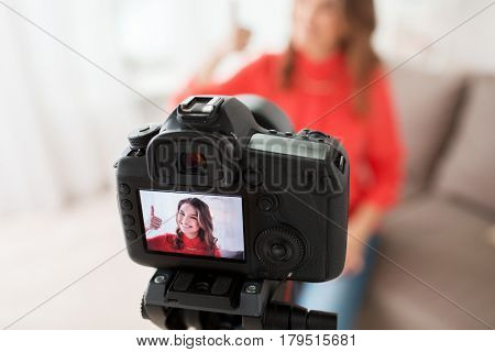 blogging, technology, videoblog, mass media and people concept - happy smiling woman or blogger with camera recording video and showing thumbs up at home