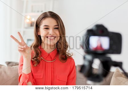 blogging, technology, videoblog, mass media and people concept - happy smiling woman or blogger with camera recording video and showing peace hand sign at home
