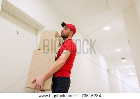 delivery, mail, people and shipment concept - man in red uniform with parcel boxes in corridor at customer door