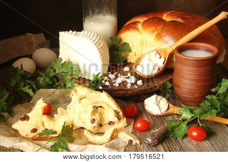 Homemade cheese fresh bread rustic milk and cottage cheese sour cream eggs on wooden boards in a rustic style