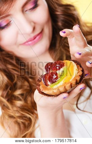 Sweetness and happiness concept. Closeup cute flirty woman eating fruit cake licks fingers yellow background