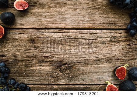 Grape and fig frame on mossy wood free space. Top view on old wooden background with ripe purple autumn fruit border. Autumn motives, harvest, gourmet concept