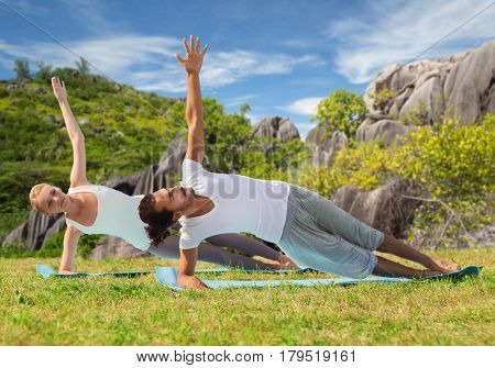 yoga, fitness, sport and people concept - couple doing plank exercise on mats outdoors