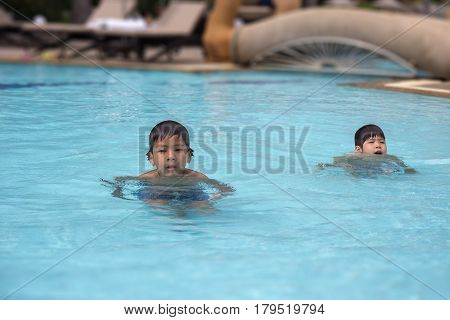 4 years and 8 years old healthy Asian kid brother swimming in clean swimming pool at sport club with copy space