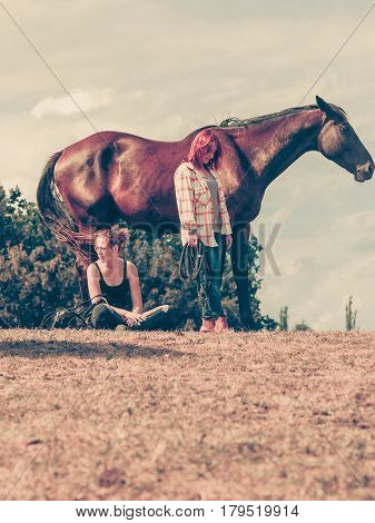 Animal and human love equine concept. Jockey woman sitting relaxing with horses on meadow and western girl.