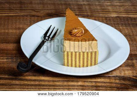 Caramel cake on plate with fork and wooden background