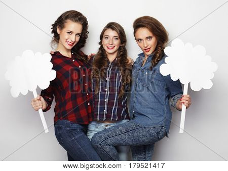 life style and people concept: stylish girls best friends holding blank paper on stick.