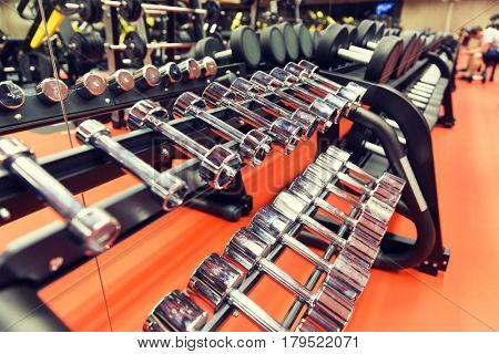 fitness, sport, exercising, weightlifting and bodybuilding concept - close up of dumbbells and sports equipment in gym
