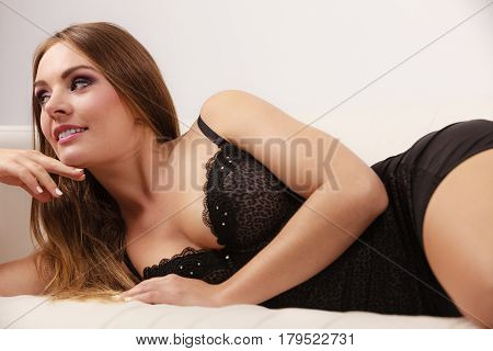 Woman sexy gorgeous alluring model lying in black luxury stylish lingerie on couch.