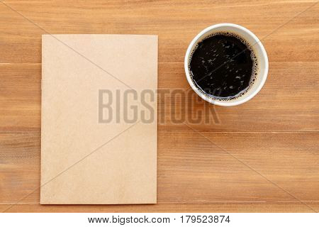 blank cover book and cup of black coffee on brown wooden background