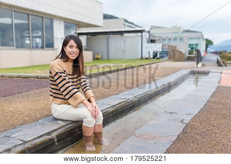 Young Woman enjoy foot onsen with cat at outdoor