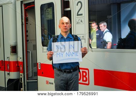 Munich,Germany-September 12,2015:A man standing by a train holds a sign protesting agains the government's policy of admitting refugees into the country