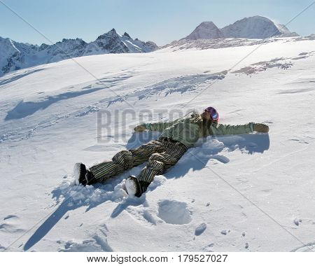 Silhouette of young woman snowboarder lying down on snow moving her arms and legs up and down creating a snowy angel figure at the ski resort of Elbrus