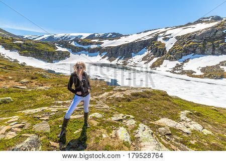 A woman turist  posing in front of frozen lake on the beautiful scenic road to the National Park Folgefonna. Norway.