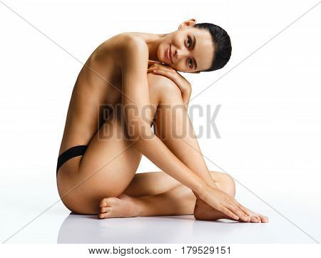 Smiling sexy woman with perfect body on white background. Beautiful female sitting on the floor touch leg. Beauty & Skin care concept
