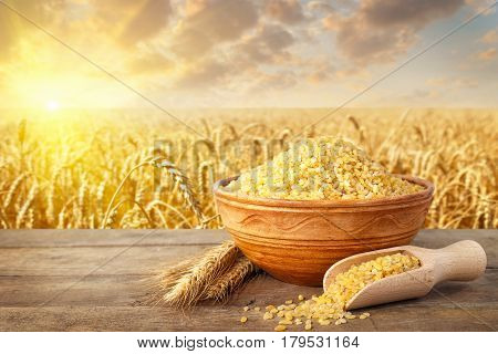 Bulgur or couscous in ceramic bowl and ears of wheat on table with ripe cereal field on the background. Agriculture and harvest concept. Golden wheat field on sunset