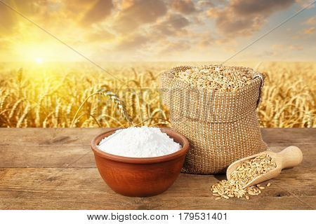 wheat grains in bag and flour in bowl on table with ripe cereal field on the background. Agriculture and harvest concept. Golden wheat field on sunset