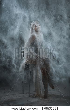 Woman sprinkled with flour in a dark room.