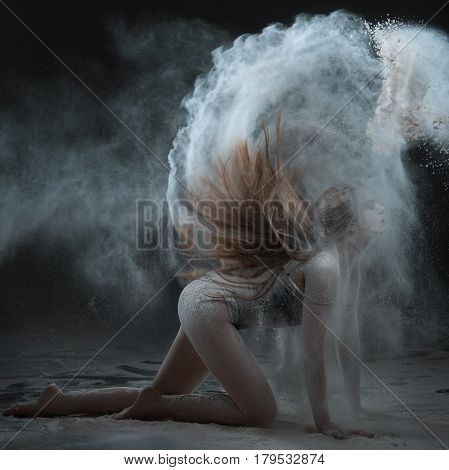 Woman shows a performance with flour. Her hair scatter the flour around the room.