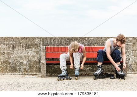 People Friends Putting On Roller Skates Outdoor.