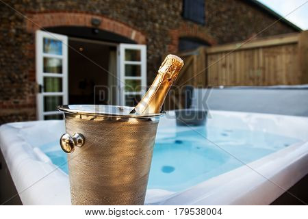 bottle of champagne cooling by hot tub