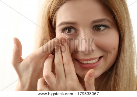 Woman putting contact lenses on white background, closeup
