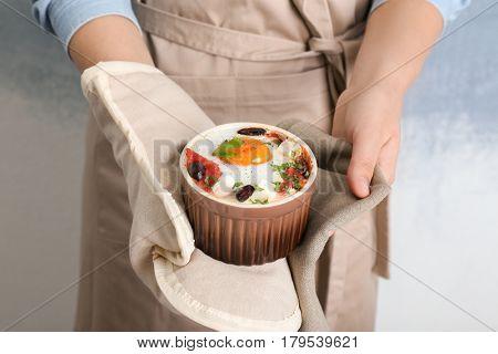 Woman holding ramekin with baked egg