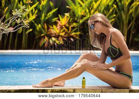 Young slim beautiful woman in bikini applying oil for sun protection.