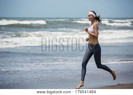 Young sporty woman running on the beach.