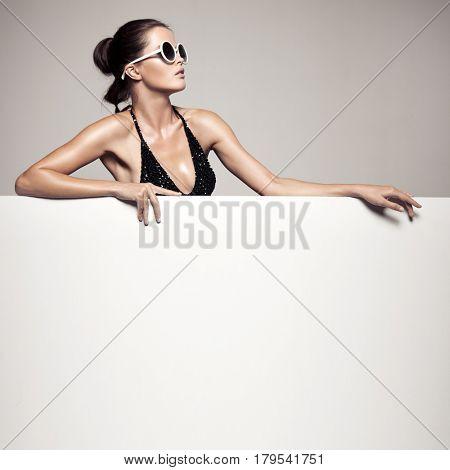 Beautiful woman in black bikini holding big empty white billboard.