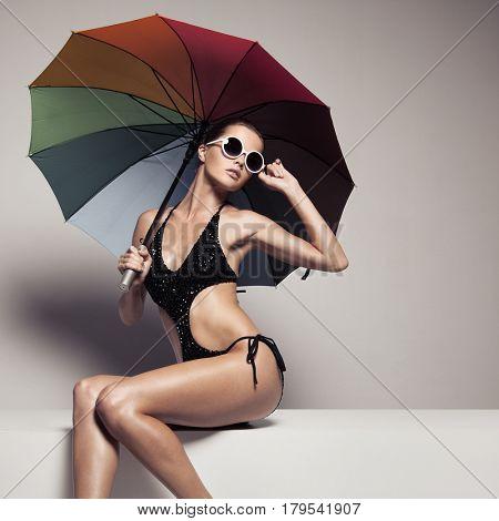 Beautiful woman in stylish black swimwear and sunglasses holding colorful umbrella. Perfect slim tanned body.