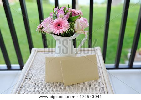 Beautiful flowers in white vase and two letters
