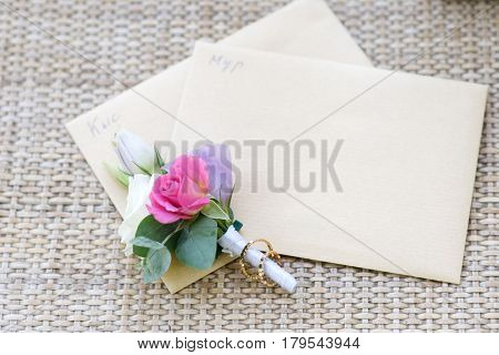 Groom boutonniere and wedding rings in wedding day