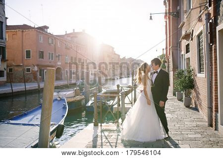 Tender bride and groom in a sunny day in Venice Italy