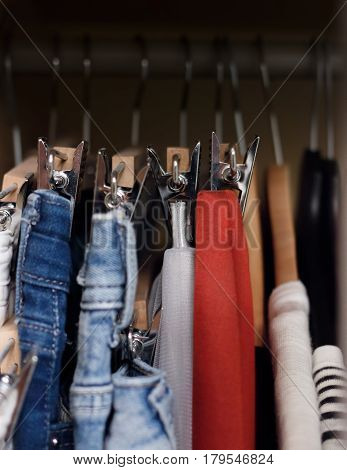 Various clothes hanged in wardrobe. Clothes hang in the closet. Jeans and skirts on chrome plated clothespins. Tightly hanging clothes in the wardrobe.