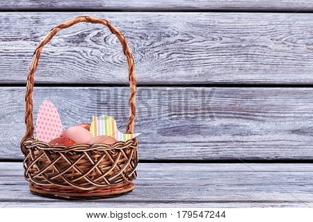 Easter basket, gray wood background. Bird and egg paper cutouts.