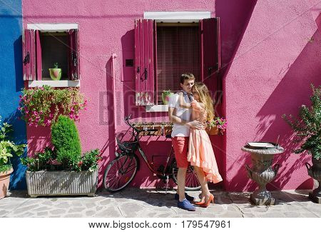 Young couple embracing near a funny purple house in Burano island Venice Italy