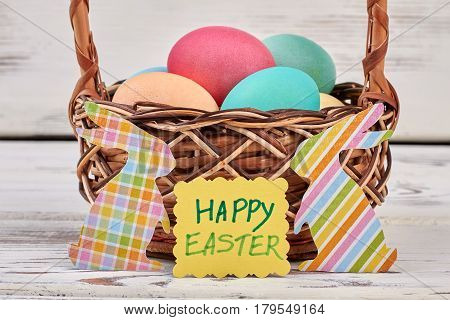 Happy Easter card, egg basket. Colorful paper rabbit cutouts.