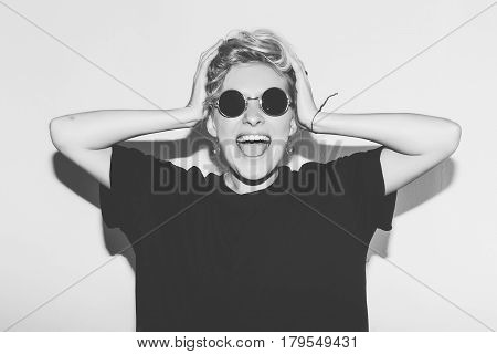 Stylish fashion sexy blonde bad crazy girl in a black t-shirt and rock sunglasses scream holding her head. Dangerous rocky emotional woman. Black and white toned. White background, not isolated