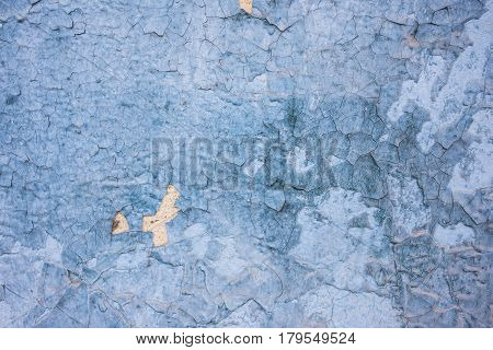 Background texture from a peeling blue paint with yellow impregnations