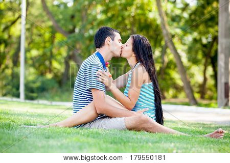 Photo Of Cute Couple Sitting And Kissing On The Grass On The Trees Background