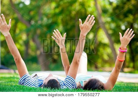 Photo Of Cute Couple Raising Their Hands And Lying On The Grass In The Field