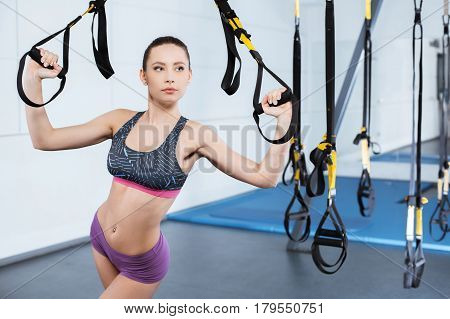 Photo of beautiful young sporty woman. Woman training with TRX Suspension at fitness club