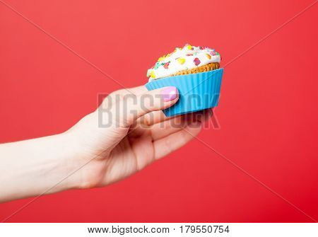 photo of female hand holding cupcake on the wonderful red background