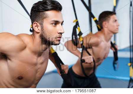 Photo of handsome young men. Sporty people training with TRX Suspension at fitness club