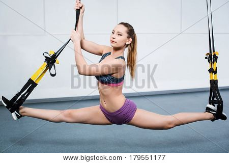 Photo of beautiful young sporty woman. Woman training with TRX Suspension at fitness club. Woman doing the splits