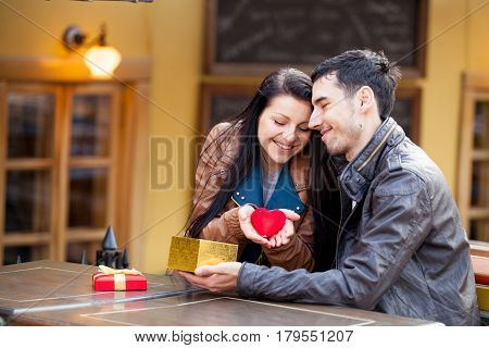 Photo Of Cute Couple Sitting On The Bench And Holding Heart Shaped Toy On The Wonderful Cafe Backgro
