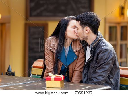 Photo Of Cute Couple Sitting On The Bench And Kissing On The Wonderful Cafe Background