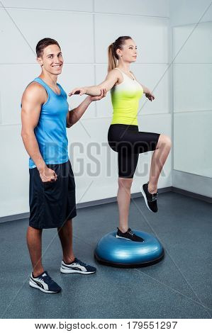 Photo of beautiful young sporty woman. Fitness girl working out with bosu at fitness club. Trainer helping woman