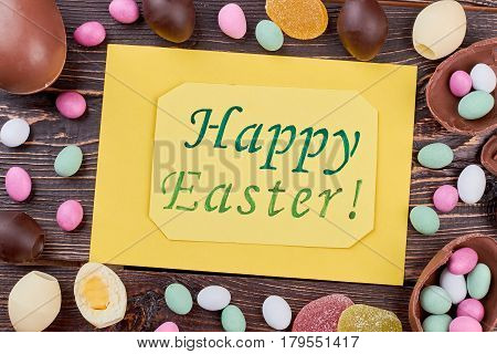 Sweets and Easter greeting card. Colorful candies on wood. Easter goodies recipes.